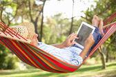 Homem sênior relaxante numa rede com e-book — Foto Stock