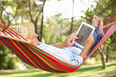 Senior Man Relaxing In Hammock With E-Book — Photo