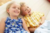 Two Children Lying Upside Down On Sofa At Home — Stock Photo