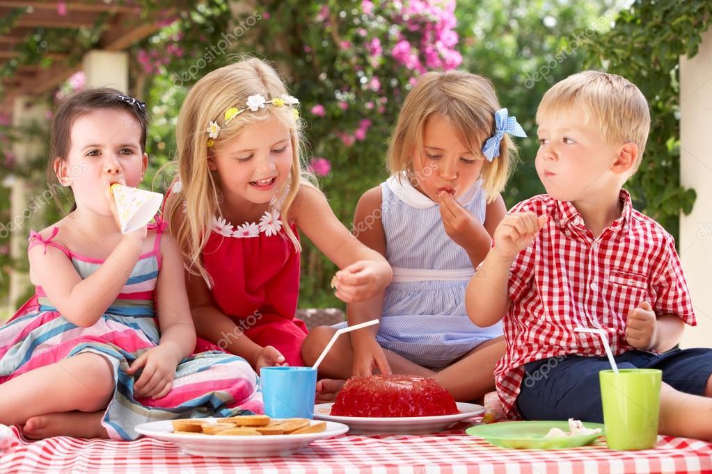 Grupo De Niños Comiendo Gelatina En Fiesta De Té Al Aire