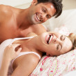 Couple Relaxing Together In Bed — Stock Photo #24640041