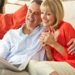 Stock Photo: Senior Couple Relaxing On Sofa At Home Reading Newspaper