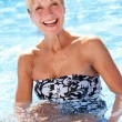 Senior Woman Having Fun In Swimming Pool - Stock Photo