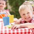 Group Of Children Enjoying Outdoor Tea Party — Stock Photo #24640149