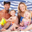 Family Sheltering From Sun Under Beach Umbrella — Stock Photo