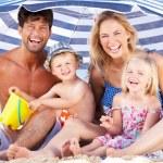 Family Sheltering From Sun Under Beach Umbrella — Stock Photo