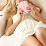 Woman Sitting On Sofa Reading Diary — Stock Photo #24640233