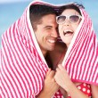 Stock Photo: Couple Sheltering From Sun On Beach Holiday
