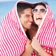 Couple Sheltering From Sun On Beach Holiday - Stock Photo
