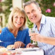Senior Couple Enjoying Meal outdoorss — Stock Photo #24640337