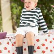 Stock Photo: Young Boy Wearing Wellington Boots Sitting On Table