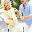 Senior Couple Juggling Oranges In Front Of Wheelbarrow — Stock Photo