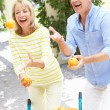 Senior Couple Juggling Oranges In Front Of Wheelbarrow - Stock Photo