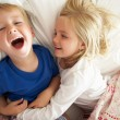 Brother And Sister Relaxing Together In Bed — Stock Photo #24640445