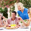 Group Of Young And Senior Couples Enjoying Family Meal — Stock Photo #24640487