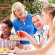 Group Of Young And Senior Couples Enjoying Family Meal — Stock Photo #24640573