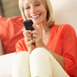 Senior Woman Relaxing On Sofa Sending Text Message — Stock Photo #24640621