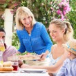 Senior Woman Serving At Multi Generation Family Meal — Stock Photo #24640625