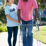 Teenage Volunteer Helping Senior Man With Walking Frame — Stock Photo