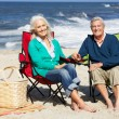 Senior Couple Sitting On Beach In Deckchairs Having Picnic — Stock fotografie