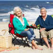 Senior Couple Sitting On Beach In Deckchairs Having Picnic — 图库照片
