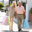 Senior Couple Carrying Shopping Bags - Stock Photo
