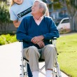 Teenage Volunteer Pushing Senior Man In Wheelchair — Stock Photo