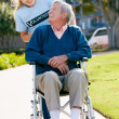 Teenage Volunteer Pushing Senior Man In Wheelchair - Stock Photo