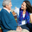 Senior MSitting On Bench With Adult Daughter By Sea — Stock Photo #24644815
