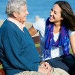 Stock Photo: Senior MSitting On Bench With Adult Daughter By Sea