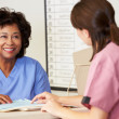 Two Nurses In Discussion At Nurses Station - Stock Photo