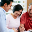 Stock Photo: Financial Advisor Talking To Senior Couple At Home