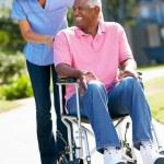 Carer Pushing Senior Man In Wheelchair — Stock Photo #24645033