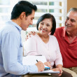 Financial Advisor Talking To Senior Couple At Home - 