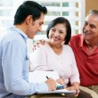 Financial Advisor Talking To Senior Couple At Home - Lizenzfreies Foto