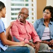 Foto de Stock  : Nurse Making Notes During Home Visit With Senior Couple