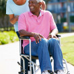 Senior Woman Pushing Husband In Wheelchair — Stock Photo #24645519