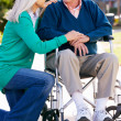 Stock Photo: Senior WomPushing Husband In Wheelchair