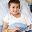 Boy Relaxing In Hospital Bed With Digital Tablet — Stockfoto