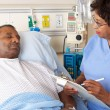 Nurse Talking To Senior Male Patient On Ward - Stock Photo