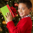 Boy Holding Christmas Present In Front Of Tree — 图库照片