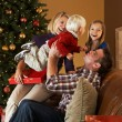 Foto Stock: Family Opening Presents In Front Of Christmas Tree