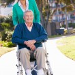 Senior Woman Pushing Husband In Wheelchair — Stock Photo