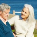 年配の女性がベンチに座って意気消沈した夫を慰める — ストック写真 #24646277