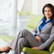 Portrait Of Businesswoman Sitting On Sofa In Modern Office - Stockfoto