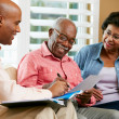 Financial Advisor Talking To Senior Couple At Home — Stock Photo #24646571