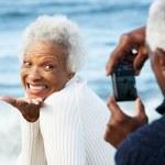 Senior Couple With Camera On Beach — Stock Photo #24646749
