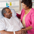 Stock Photo: Senior Wife Visiting Husband On Ward
