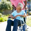 Stock Photo: Senior WomPushing Unhappy Husband In Wheelchair