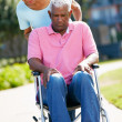 Senior Woman Pushing Unhappy Husband In Wheelchair — Stock Photo #24647025
